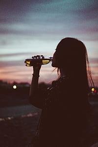 girl wearing black 3/4-sleeved top drinking black labeled plastic bottle