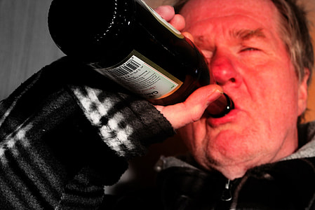 man wearing black zip-up jacket drinking on black and white labeled glass bottle