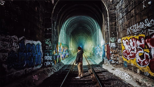 man standing in middle of train track tunnel