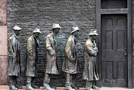 five men statue lining up near door photo