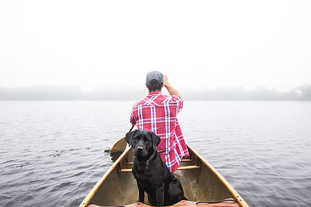 man wearing red and white plaid sport shirt riding boat