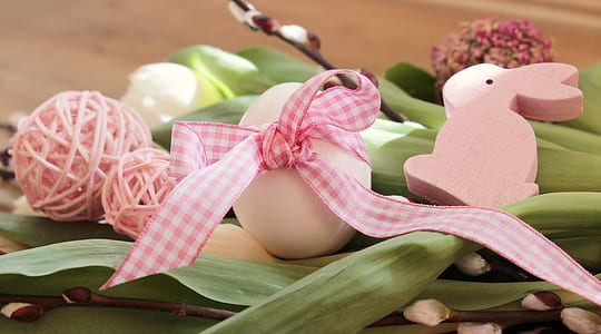 white and pink Easter bunny-themed decoration on green leaf