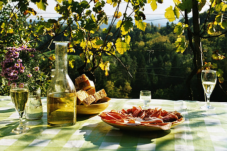 sliced meat on plate beside wine