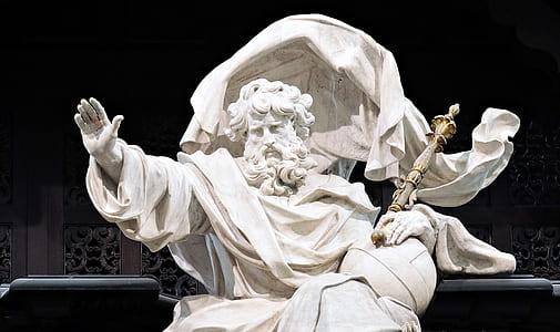 man sitting holding wand statue