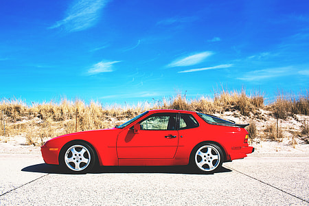 A red sports car sits on the road