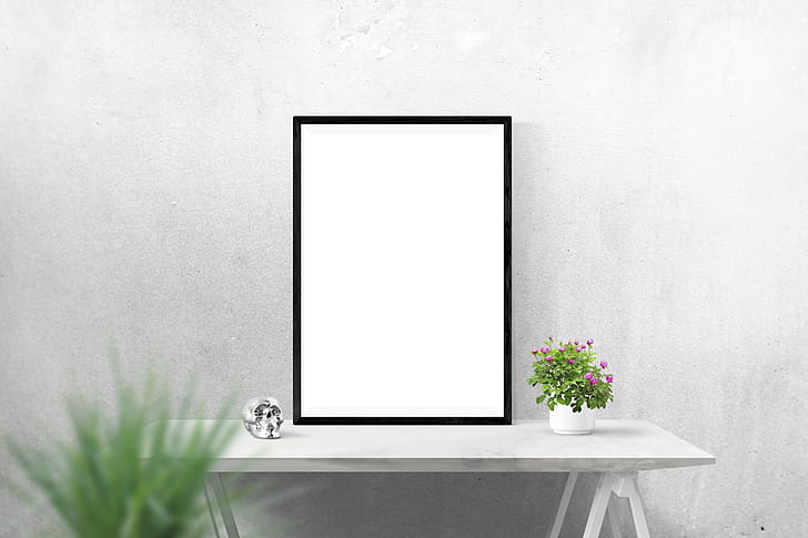 Royalty-Free photo: Plain white canvas with black frame on table ...