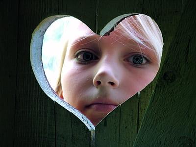 closeup photo of girl peeping on heart hole
