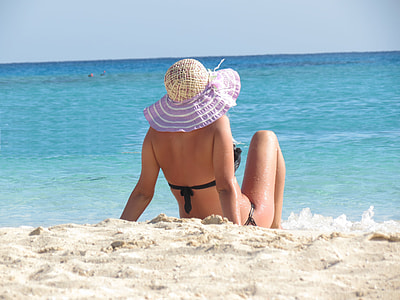 sitting woman with black bikini on seashore during daytime