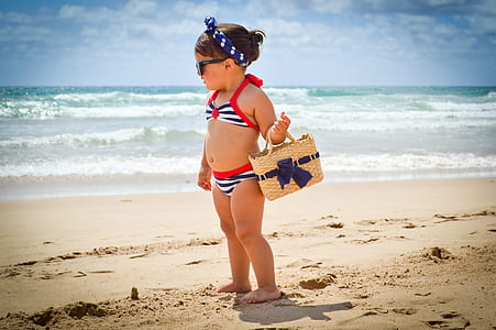 girl carrying beige wicker basket on beach shore during daytime