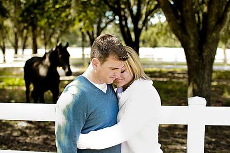woman wearing white sweater hugging man wearing blue sweater
