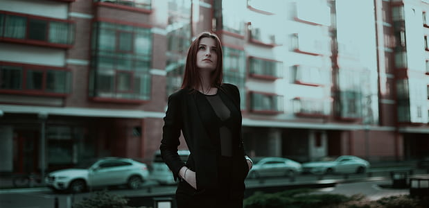woman wearing black long-sleeved dress standing near building at daytime
