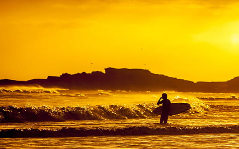 man holding surfboard during sunset