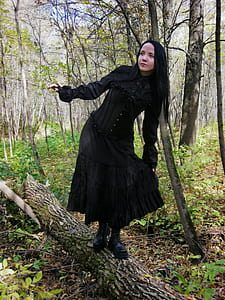 woman wearing black dress standing on brown tree log