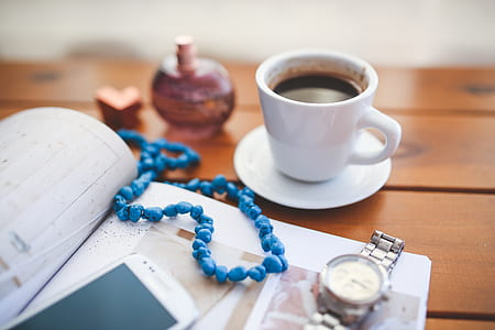 beaded blue necklace on book between white cup with coffee and analog watch