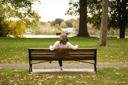 woman sitting on bench at outside park