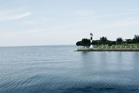body of water near green island and lighthouse at daytime