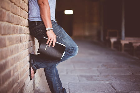 man holding book leaning on bricks