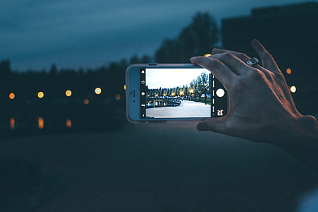 Woman photographer taking a photo with her iPhone camera at night