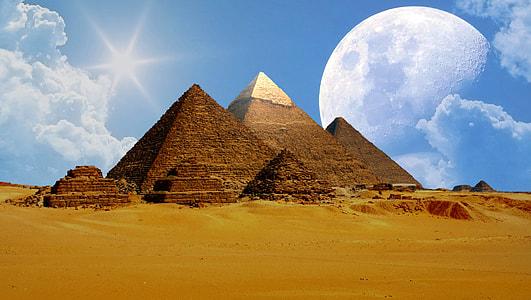 brown pyramids under white cloudy sky