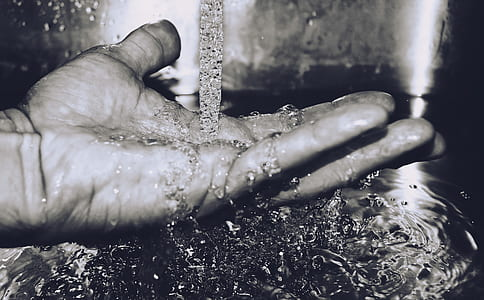 grayscale photography of pouring water on hand
