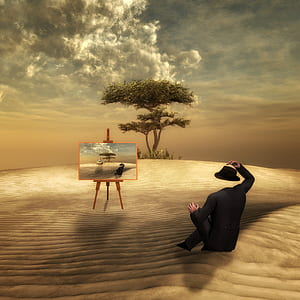 headless man sitting on ground near painting on easel with tall tree background