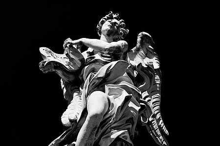 High-contrast monochrome shot of a statue on the River Tiber in Rome, Italy