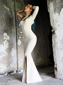 woman in white 1-shoulder long-sleeved 1-slit long dress stands beside grey concrete wall