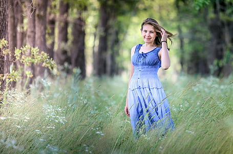 selective photography of woman wearing blue and black tank dress in green grass field
