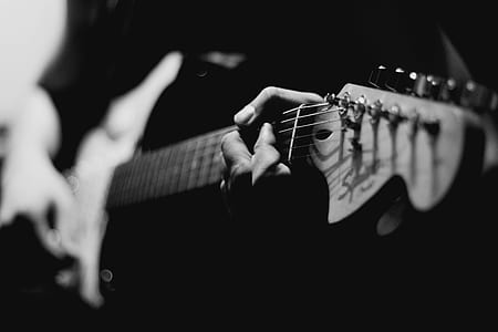 grayscale photo of man holding electric guitar