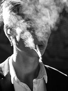 male smoking grayscale photo