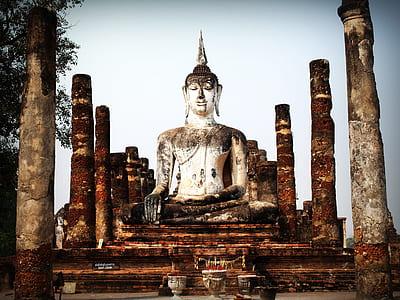 Gautama Buddha concrete statue surrounded with concrete columns