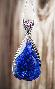 silver-colored necklace with blue gemstone
