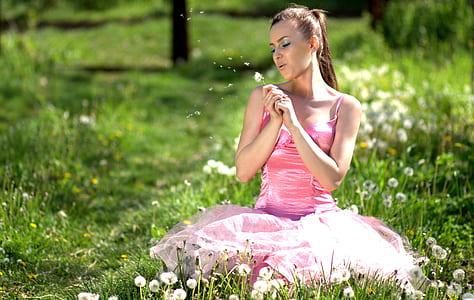 woman wearing pink spaghetti-strap dress sitting dandelion flowers