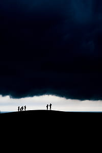 six people standing against white clouds