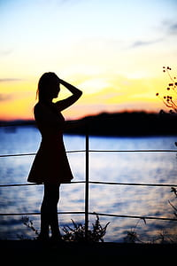 silhouette photography of woman in front of fence