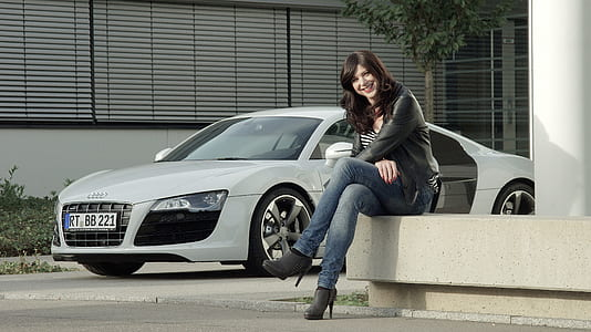 sitting woman in black leather jacket beside silver Audi sports coupe