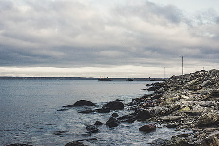 Rocks Beneath the Sea Under Cloudy Sky