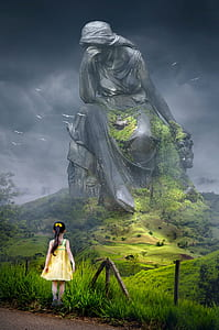 girl in yellow sundress in front of a giant woamn statue