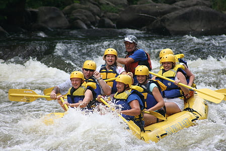 people riding inflatable boat on river