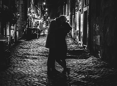 black and white photo of man and woman kissing