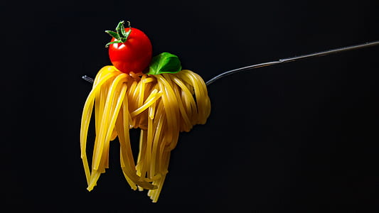 rolled pasta in gray metal fork with red cherry tomato