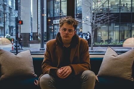man wearing brown coat sitting on blue sofa