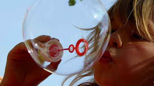 girl making bubble during daytime