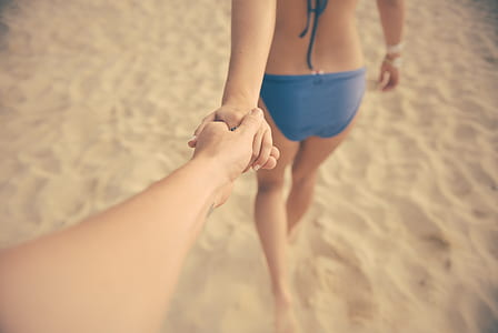 person holding woman hand in blue bikini