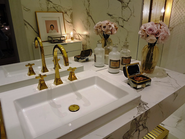 gold-colored steel faucet with white ceramic sink