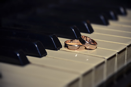 two pink gold-colored rings placed on piano keys