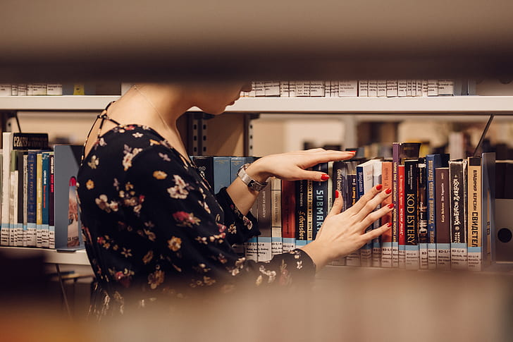 woman in black floral dress on library
