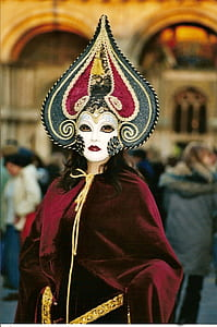 woman weawring red, white, and gray masquerade mask and red robe