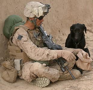 soldier sitting beside black dog
