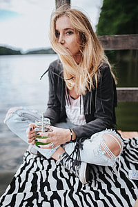 Blonde woman having a healthy snack at the wooden pier